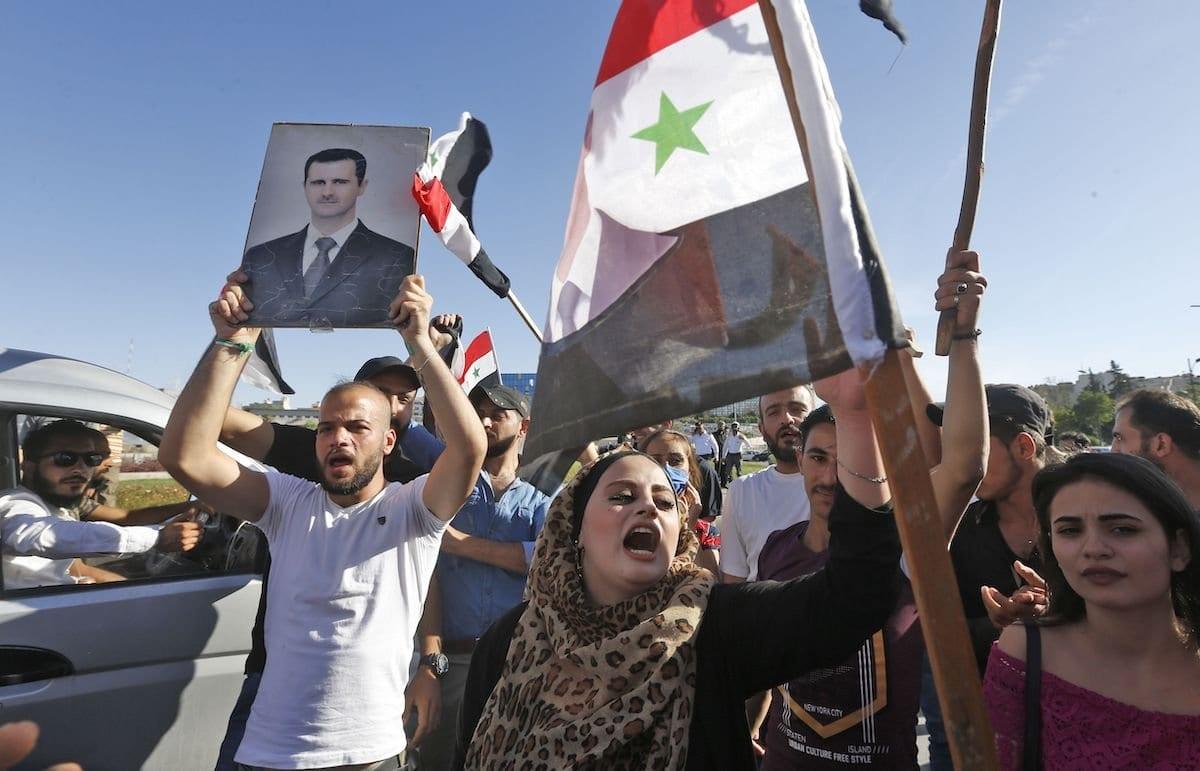 Manifestantes empunham bandeiras nacionais da Síria e fotos do presidente Bashar Al-Assad durante protesto contra as sanções dos EUA contra o país em Damasco em 11 de junho de 2020 [Louai Beshara/ AFP via Getty Images]
