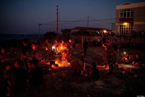 Refugiados e migrantes do campo destruído de Moria cozinham em chamas durante o início da noite na ilha de Lesbos, em 11 de setembro de 2020 [Angelos Tzortzinis/ AFP via Getty Images]