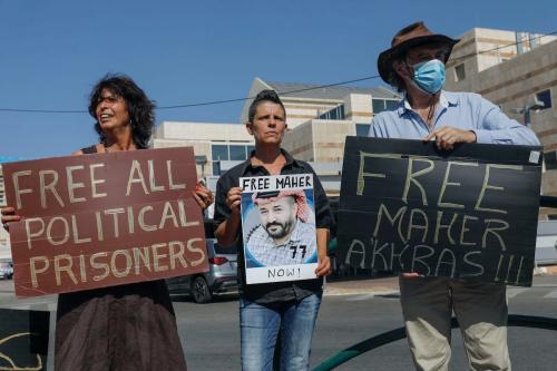 Israelenses de esquerda exibem cartazes durante protesto para pedir a libertação de palestinos mantidos sob detenção administrativa, incluindo Maher al-Akhras, cuja saúde deteriorou-se após greve de fome de 77 dias, em frente ao centro médico de Kaplan, na cidade de Rehovot, 11 de outubro de 2020 [Ahmad Gharabli/AFP/Getty Images]
