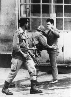 Soldados franceses revistam um civil em uma rua de Argel, durante a Guerra da Independência da Argélia [Central Press / Getty Images]