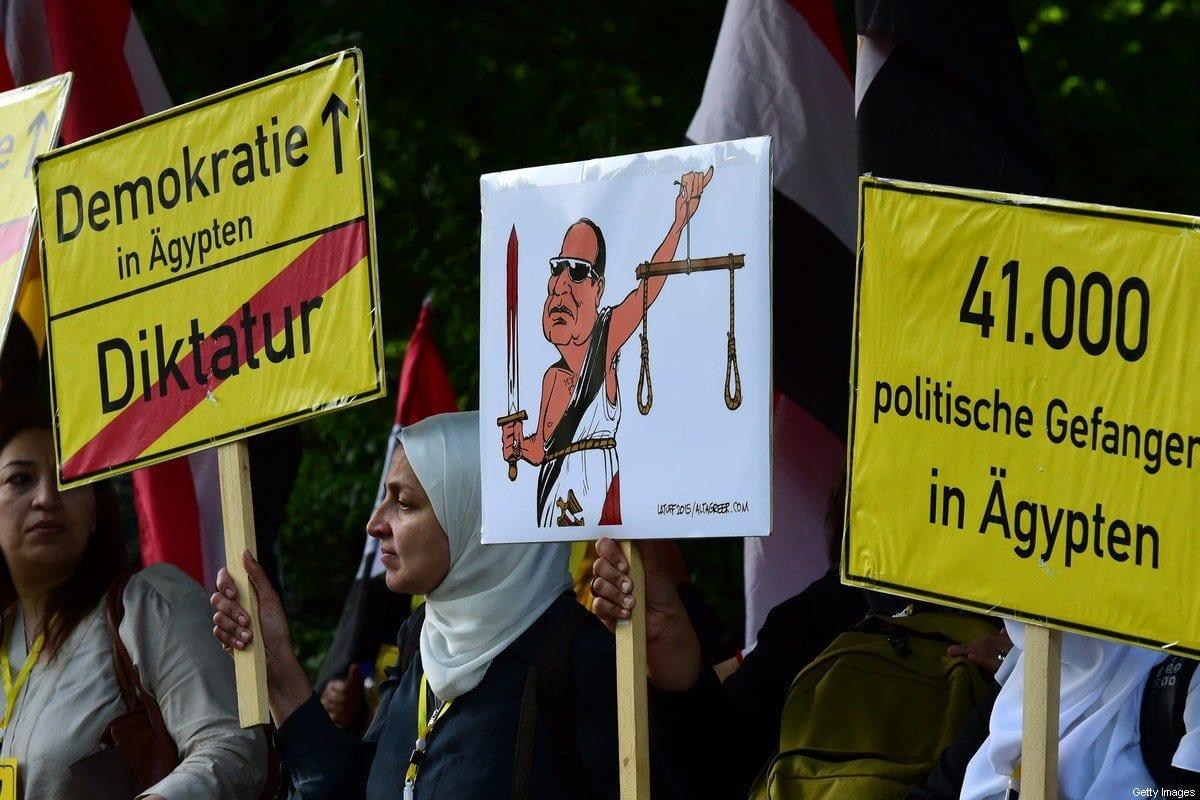 Manifestantes exibem cartazes por 'Democracia no Egito' e pela libertação de '41 presos políticos no Egito', diante da chegada do presidente egípcio Abdel Fattah el-Sisi para reunião com sua contraparte alemã, em frente ao Palácio Bellevue, em Berlim, Alemanha, 3 de junho de 2015 [John MacDougall/AFP/Getty Images]