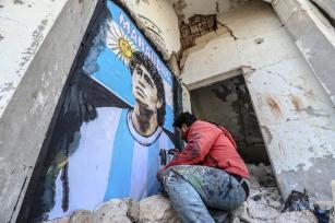 O grafiteiro Sírio Aziz Esmer desenha um retrato de Diego Armando Maradona nas paredes de uma casa destruída após os ataques das forças do regime de Assad, em Idlib, Síria, em 27 de novembro de 2020. [İzzeddin idilbi - Agência Anadolu]