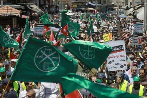 """Bandeiras da Irmandade Muçulmana, Jordânia e outras entre cartazes de protesto contra a conferência econômica do Oriente Médio, liderada pelos EUA em Bahrein, e o """"Acordo do Século"""" do presidente Donald Trump, na capital jordaniana, Amã, em 21 de junho de 2019 [Khalil Mazraawi/ AFP via Getty Images]"""