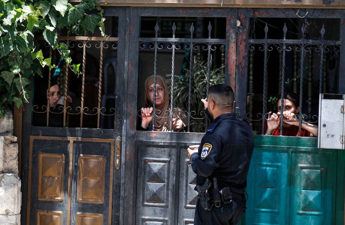 Um policial israelense do lado de fora da antiga casa de uma família palestina enquanto alguns de seus membros olham de um portão, durante seu despejo no bairro palestino de Silwan, no leste de Jerusalém, perto da Cidade Velha, em 10 de julho de 2019. [Ahmad Gharabli/ AFP via Getty Images]