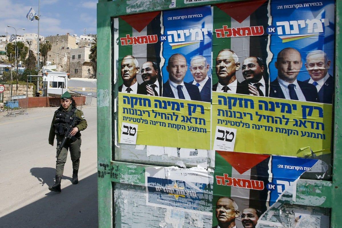 Cartazes eleitorais do líder da aliança política Azul e Branco de Israel (Kahol Lavan) Benny Gantz, exibem o membro árabe-israelense da Lista Conjunta Ahmad Tibi, Ministro da Defesa Naftali Bennett e Primeiro Ministro Benjamin Netanyahu, em Hebron em 23 de fevereiro de 2020 [Haze,Bader/ AFP via Getty Images]