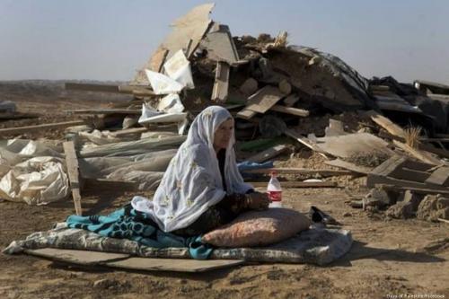 Uma mulher palestina se senta em frente à sua casa demolida por ação das forças israelenses no Negev em 15 de fevereiro de 2015 [Dias da Palestina / Facebook]