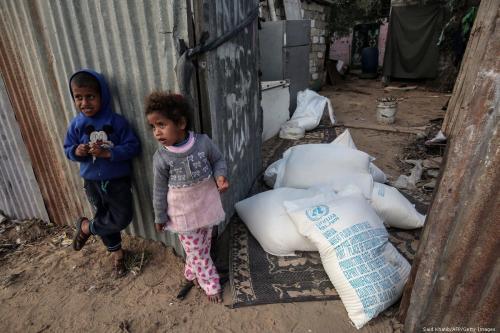 Crianças palestinas ao lado de sacos de ajuda alimentar na Faixa de Gaza, 24 de janeiro de 2018 [Said Khatib/AFP/Getty Images]