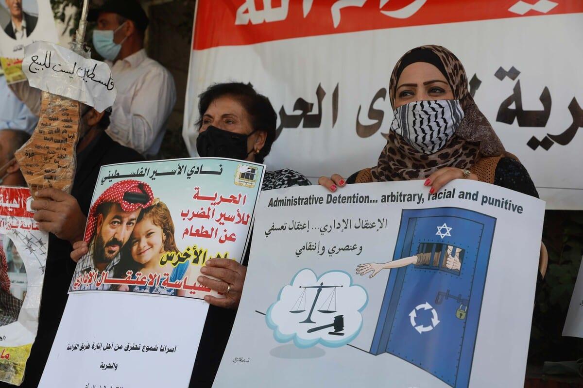 Manifestantes exibem cartazes em apoio aos presos palestinos mantidos nas cadeias israelenses, em Ramallah, Cisjordânia ocupada, 20 de outubro de 2020 [Issam Rimawi/Agência Anadolu]