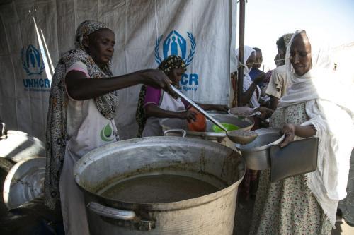 Refugiados do conflito em Tigré, norte da Etiópia, recebem assistência alimentar no campo de Hamdayit, no Sudão, 14 de dezembro de 2020 [Mahmoud Hjaj/Agência Anadolu]