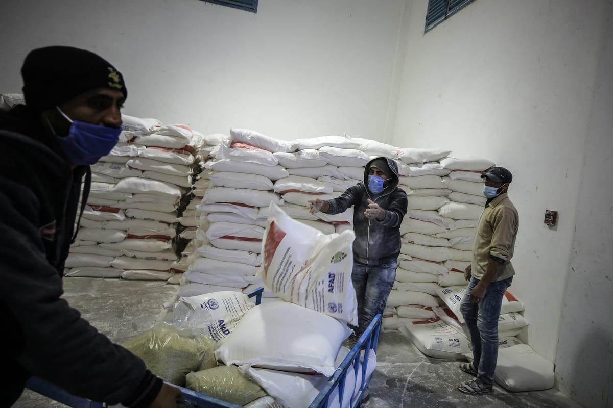 Trabalhadores da Agência das Nações Unidas de Assistência aos Refugiados da Palestina (UNRWA) embalam ajuda humanitária proveniente de diferentes países para distribuí-la em Jabalia, Faixa de Gaza, 17 de dezembro de 2020 [Ali Jadallah/Agência Anadolu]