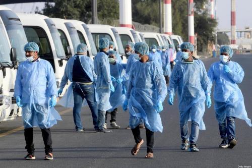 Trabalhadores do Ministério da Saúde, usando roupas de proteção, esperam na pista do Aeroporto Internacional do Kuwait para receber cidadãos retornando de Frankfurt em 26 de março de 2020 [STR / AFP via Getty Images]