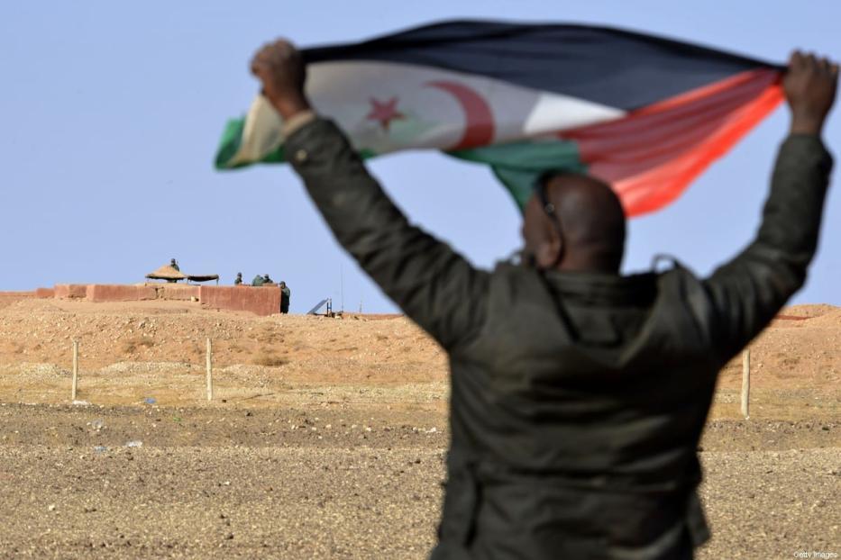Um saharaui segura uma bandeira da Frente Polisario na área de Al-Mahbes, perto dos soldados marroquinos que guardam o muro que separa o Sahara Ocidental controlado pela Polisario de Marrocos a 3 de fevereiro de 2017. [Stringer/ AFP via Getty Images]