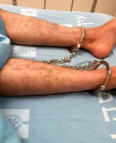 O garoto palestino, Mohammad Muqbel, acorrentado a sua cama de hospital após ser submetida a uma cirurgia devido a espancamento brutal por soldados israelenses, 4 de dezembro de 2020 [iKhaybar / Twitter]