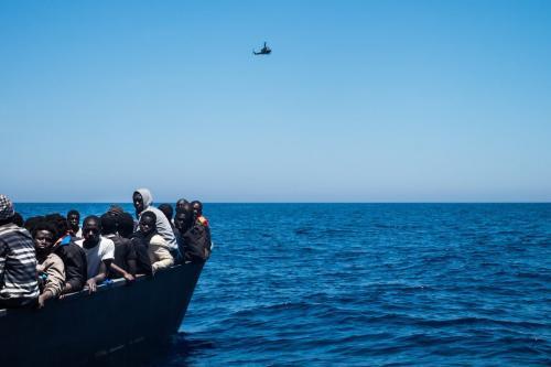 Um helicóptero líbio sobrevoa enquanto refugiados esperam para embarcar no navio de resgate no Mar Mediterrâneo, em 15 de junho de 2017. [Marcus Drinkwater/Agência Anadolu]