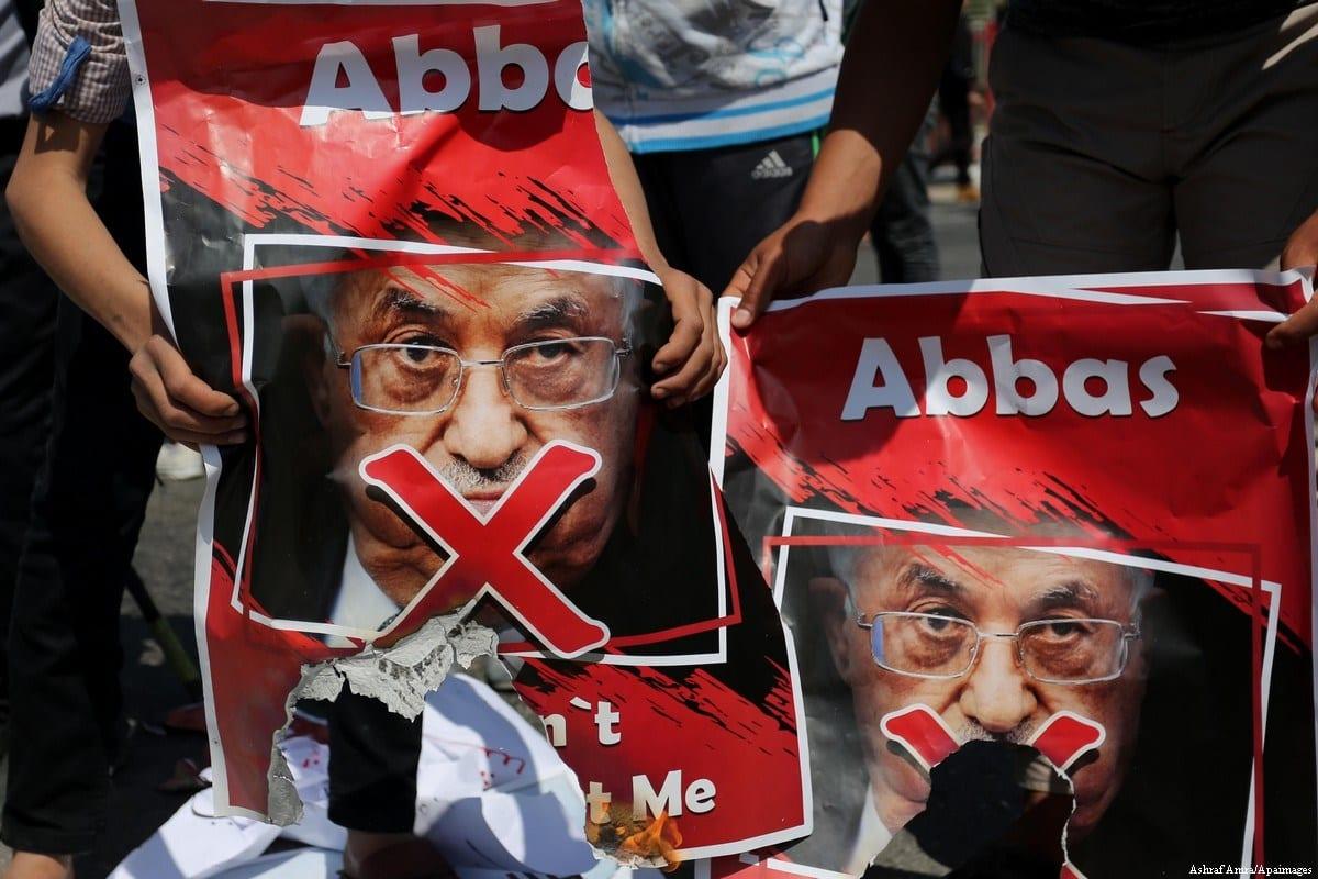 Palestinos carregam cartazes que mostram o presidente palestino Mahmoud Abbas com uma cruz vermelha durante um protesto contra ele em Gaza, em 22 de março de 2018. [Ashraf Amra/Apaimages]