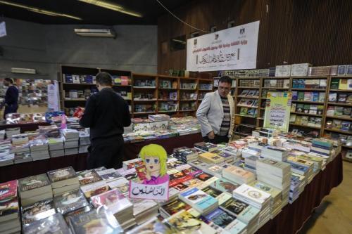 """Palestinos visitam o Centro Cultural Rashad Al Shawwa durante a feira do livro """"Gazzetu Hashim"""", que foi aberta apesar das condições limitadas devido ao bloqueio israelense, na Cidade de Gaza, Gaza em 14 de abril de 2019. Mais de 10 estabelecimentos e editoras participaram da feira [Mustafa Hassona / Agência Anadolu]"""