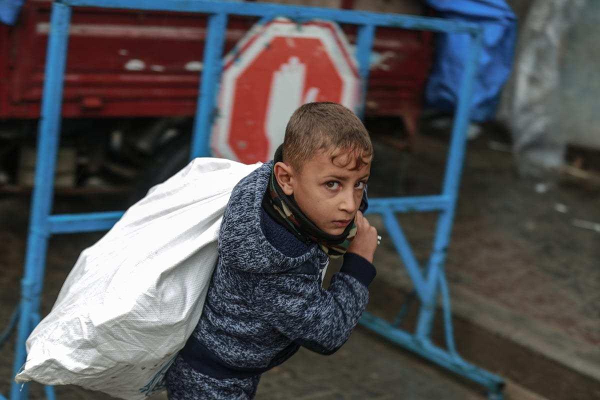 Um menino carrega um saco enquanto trabalhadores da Agência das Nações Unidas para os Refugiados da Palestina (UNRWA) distribuem ajuda humanitária em Jabalia, Gaza, em 17 de dezembro de 2020 [Ali Jadallah / Agência Anadolu]