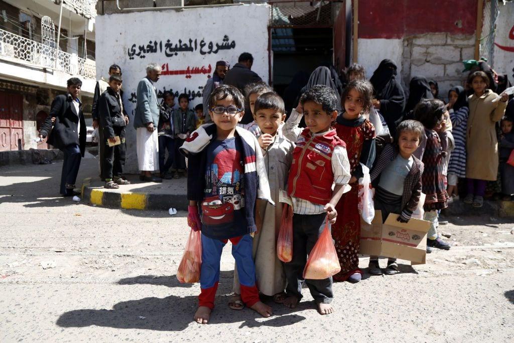 Crianças iemenitas carregam seu almoço oferecido por uma instituição de caridade em Sana'a, Iêmen, em 3 de novembro de 2018 [Mohammed Hamoud / Getty Images]