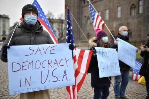"""Pessoas usando máscaras protetoras acenando bandeiras americanas e segurando cartazes de protesto onde se lê """"Trump, vá para casa"""" e """"Salve a democracia nos EUA"""", na Piazza Castello, em 09 de janeiro de 2021, em Torino, Itália. [Stefano Guidi/Getty Images]"""