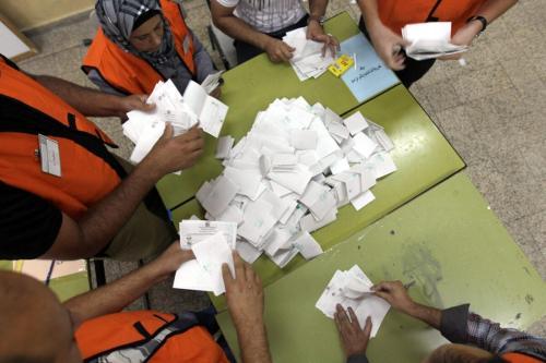 Funcionários do comitê eleitoral palestino separam cédulas de voto após o fechamento das urnas na aldeia de Deir al-Hatab, norte da Cisjordânia ocupada, em 20 de outubro de 2012 [Jaafar Ashtiyeh/AFP/Getty Images]