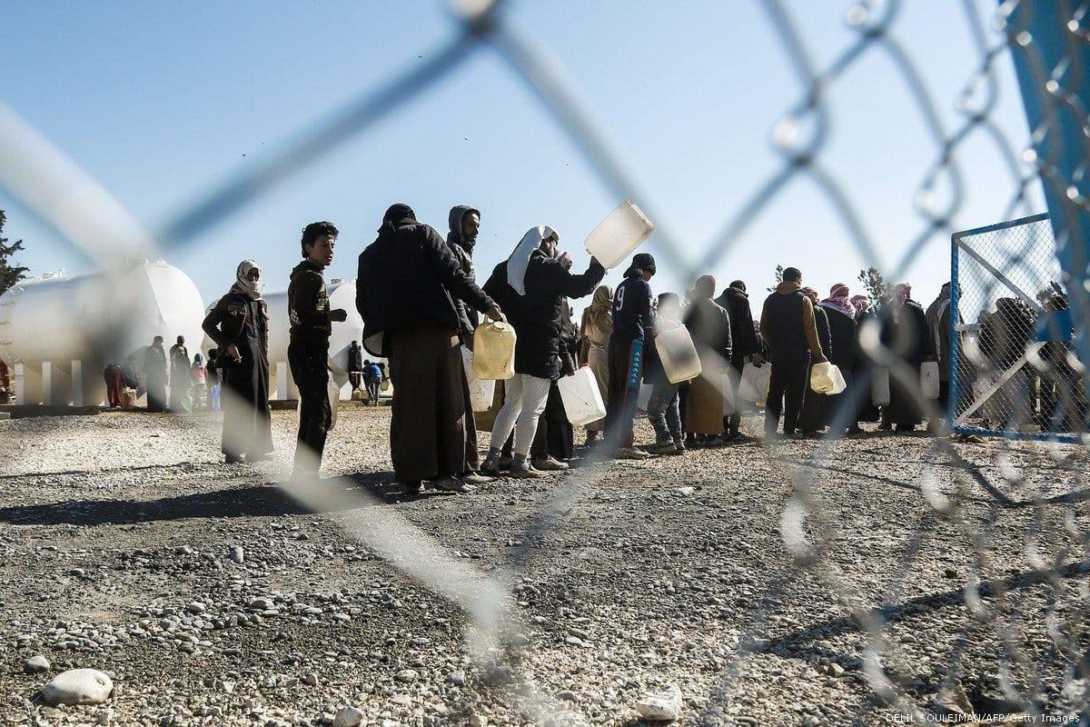Sírios aguardam em fila para receber água, no campo de refugiados de Al-Hawl, na Síria, em 29 de janeiro de 2017 [Delil Souleiman/AFP/Getty Images]