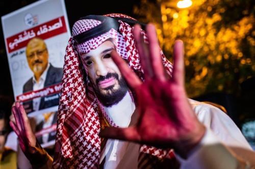 Manifestante usa uma máscara com o rosto de Mohammad Bin Salman, príncipe herdeiro e governante de fato da Arábia Saudita, e exibe mãos vermelhas de 'sangue', em protesto contra o assassinato do jornalista saudita Jamal Khashoggi, em 25 de outubro de 2018 [Yasin Akgul/AFP via Getty Images]