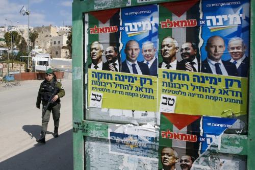 Cartazes eleitorais do líder da aliança política Azul e Branco de Israel (Kahol Lavan) Benny Gantz, com o membro árabe israelense da Lista Conjunta Ahmad Tibi, e do ministro da DefesaiIsraelense, Naftali Bennett e o primeiro-ministro Benjamin Netanyahu, em Hebron em 23 de fevereiro de 2020 [Hazem Bader/ AFP via Getty Images]