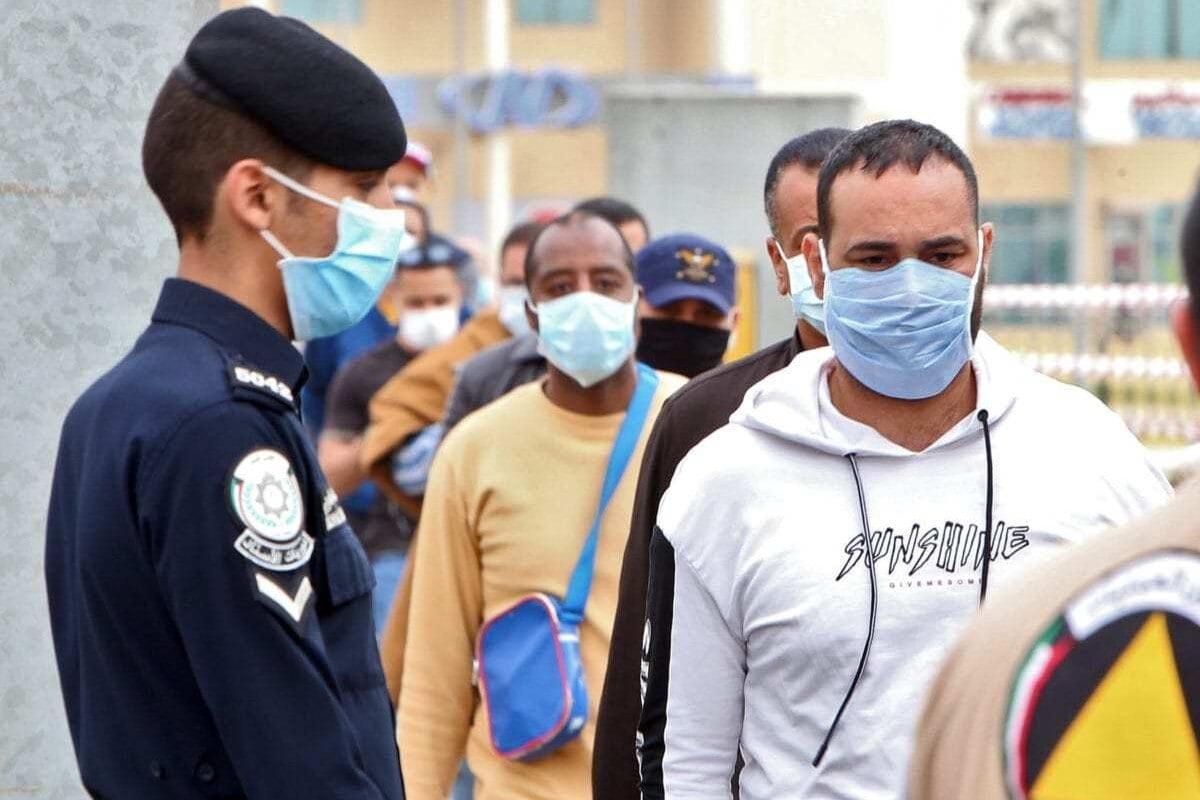 Trabalhadores imigrantes em fila em um centro de confinamento e testagem para covid-19, estabelecido pelo Ministério da Saúde do Kuwait na capital do país, em 15 de março de 2020 [Yasser al-Zayyat/AFP/Getty Images]