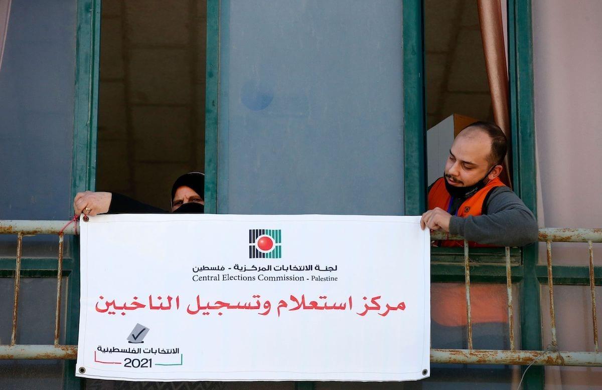 """Membros da Comissão Eleitoral Central Palestina penduram uma placa em árabe onde se lê """"centro de informações e registro de eleitores"""" na cidade de Hebron, na Cisjordânia, em 10 de fevereiro de 2021. [Hazem Bader/AFP via Getty Images]"""