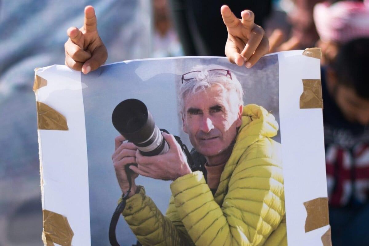 Um homem faz o sinal da vitória atrás de uma foto de Herve Gourdel, o caminhante decapitado por militantes argelinos ligados ao grupo do Estado Islâmico em Marselha, no sul da França. [Bertrqand Langlois/AFP via Getty Images]