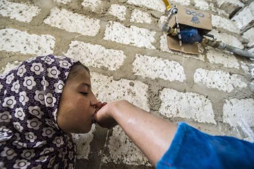 Uma mãe egípcia coloca suas mãos sob uma torneira aberta em seu quintal para que sua filha de seis anos possa beber água, no vilarejo de al-Jendaya. Cidade de Bani Mazar, na província de Minya, a cerca de 200 km ao sul do Cairo, no dia 5 de abril de 2016. [KHALED DESOUKI/AFP via Getty Images]