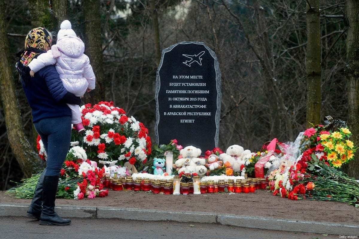 Uma mulher com um bebê em frente à pedra fundamental de um Jardim da Memória em homenagem às 224 pessoas mortas no bombardeio de um avião russo sobre o Egito em 31 de outubro de 2016 na cidade de Vsevolozhsk nos arredores de São Petersburgo [Ola Matves/AFP via Getty Images]