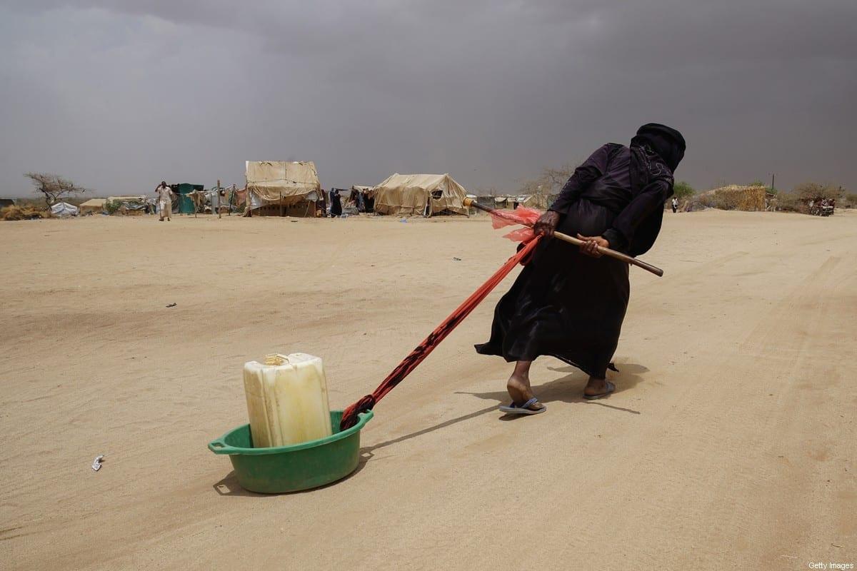 Refugiada iemenita arrasta um galão de água à sua tenda, no campo de deslocados internos de Abs, situado a 40 km da frente de batalha com a Arábia Saudita [Giles Clarke/UNOCHA/Getty Images]