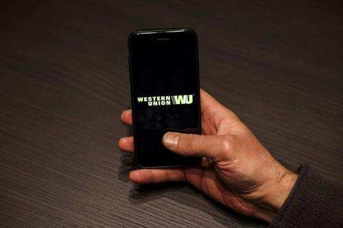 Uma pessoa segura uma tela de celular exibindo o logotipo da Western Union, em Ancara, Turquia, em 30 de novembro de 2020. [Binnur Ege Gürün Koçak/Agência Anadolu]