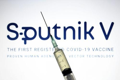 Sputnik V (Gam-COVID-Vac), o logotipo da vacina de covid-19 é exibido em uma tela com uma seringa na frente. [Hakan Nural/Anadolu Agency]