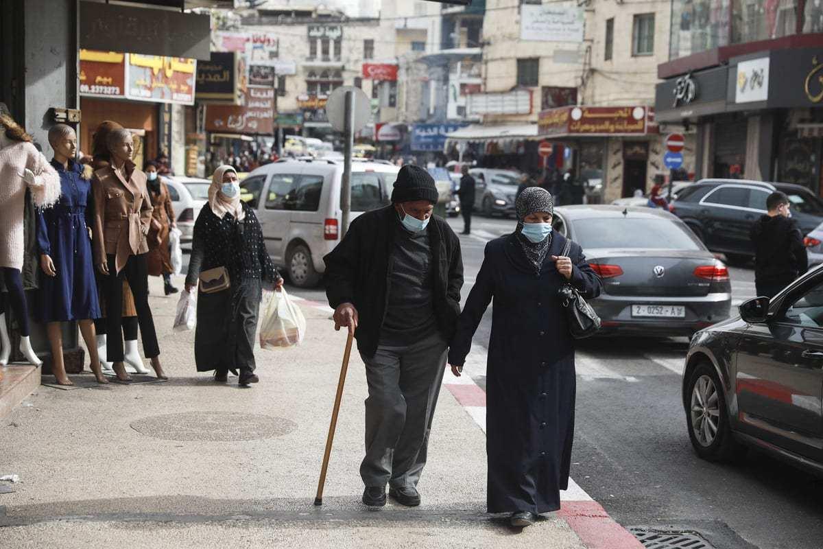 Palestinos usam mascaras como medida contra o novo tipo de coronavírus (Covid-19) pandemia em Ramallah, Cisjordânia em 30 de janeiro de 2021 [Issam Rimawi / Agência Anadolu]