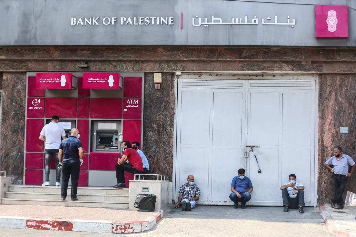 Palestinos vestem máscaras de proteção e mantêm distanciamento social em fila para um caixa eletrônico, na Cidade de Gaza, 1° de setembro de 2020 [Ali Jadallah/Agência Anadolu]