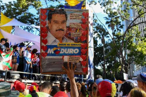 Manifestante exibe cartaz em apoio ao Presidente da Venezuela Nicolás Maduro, durante marcha contra o Tratado Interamericano de Assistência Recíproca (TIAR), em Caracas, 3 de dezembro de 2019 [Yuri Cortez/AFP via Getty Images]