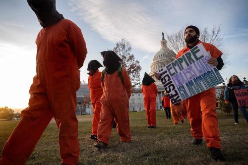"""Manifestantes vestidos com uniformes de prisioneiros da Baía de Guantánamo marcham pelo Capitólio em Washington, DC, em 9 de janeiro de 2020, durante um comício sobre """"Sem Guerra com o Irã"""". [Jim Watson/ AFP via Getty Images]"""