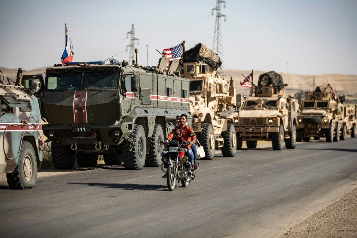 Um casal passa de moto pelos veículos militares russos e americanos na cidade de al-Malikiyah (Derik), no nordeste da Síria, na fronteira com a Turquia, em 3 de junho de 2020. [Delil Souleiman/AFP via Getty Images]