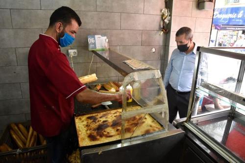 Um argelino compra um sanduíche em uma loja na capital Argel, em 7 de junho de 2020. [Ryad Kramdi/AFP via Getty Images]