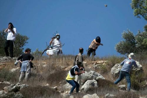 Colonos israelenses atacam fazendeiros palestinos da aldeia de Hawara, perto do assentamento de Yitzhar, Cisjordânia ocupada, 7 de outubro de 2020 [Jaafar Ashtiyeh/AFP/Getty Images]