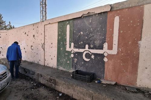 Voluntário líbio participa de uma operação para renovar a escola dos Mártires da Líbia em 19 de novembro de 2020 [Mahmud Turkia/ AFP / Getty Images]