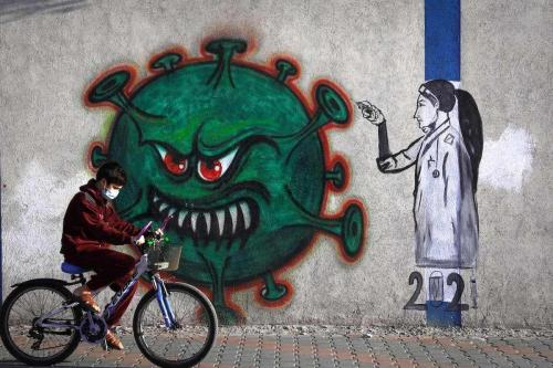 Um jovem palestino de máscara anda com sua bicicleta em frente a um grafite representando a vacinação contra o covid-19, na Cidade de Gaza, 31 de dezembro de 2020 [Mohammed Abed/AFP/Getty Images]