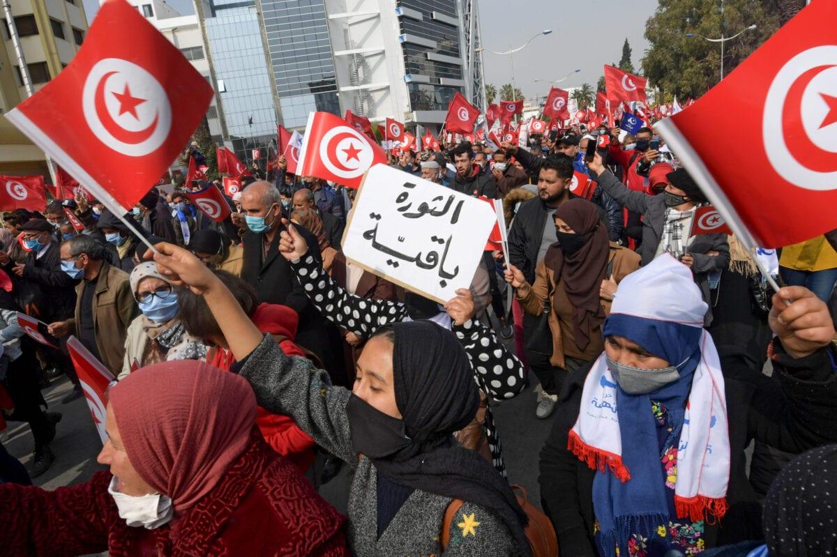 """Apoiadores do partido islâmico Ennahdha carregam um cartaz que diz """"A revolução está ficando"""" durante uma manifestação de apoio ao governo tunisiano em 27 de fevereiro de 2021 na capital Túnis [Fethi Belaid/ AFP via Getty Images]"""