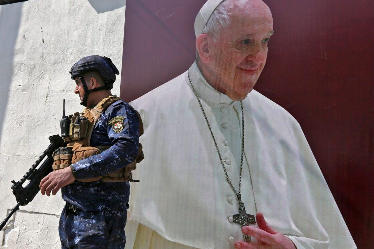 Um membro das forças iraquianas está ao lado de um pôster retratando uma imagem do Papa Francisco na Igreja Católica Siríaca de Nossa Senhora da Libertação, no distrito de Karrada, capital do Iraque, Bagdá, em 1º de março de 2021, em meio aos preparativos para a visita do pontífice. [Sabah Arar/AFP via Getty Images]