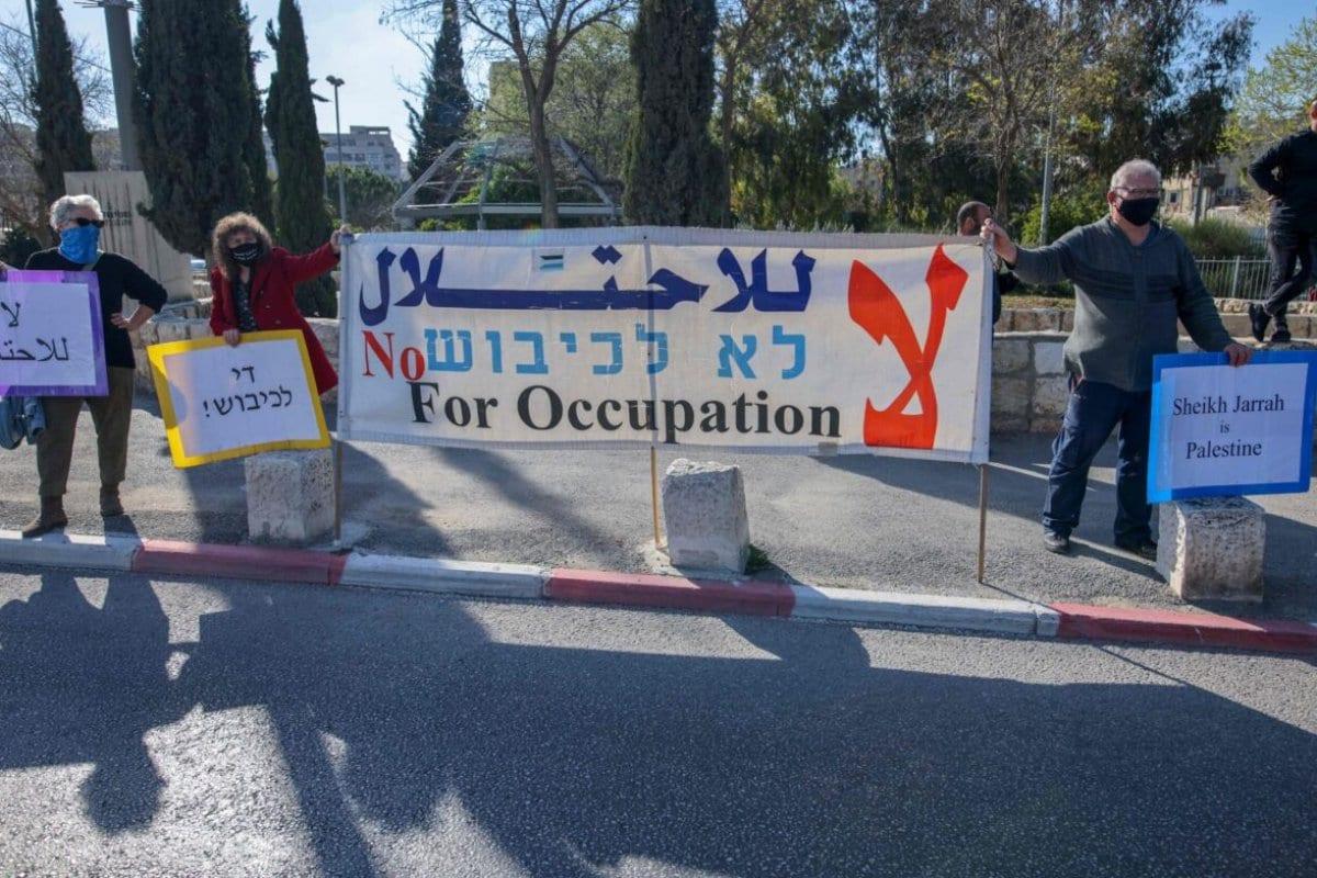 Ativistas palestinos, israelenses e estrangeiros erguem faixas e cartazes durante uma manifestação contra a ocupação israelense e atividades de assentamento nos Territórios Palestinos e em Jerusalém oriental, no bairro de Sheikh Jarrah palestino, em Jerusalém, em 19 de março de 2021. [Ahmad Gharabli/AFP via Getty Images]