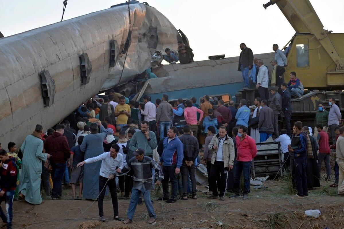 Pessoas se reúnem ao redor dos destroços de dois trens que colidiram no distrito de Tahta, na província de Sohag, matando pelo menos 18 pessoas e ferindo várias outras, em 26 de março de 2021. [AFP via Getty Images]