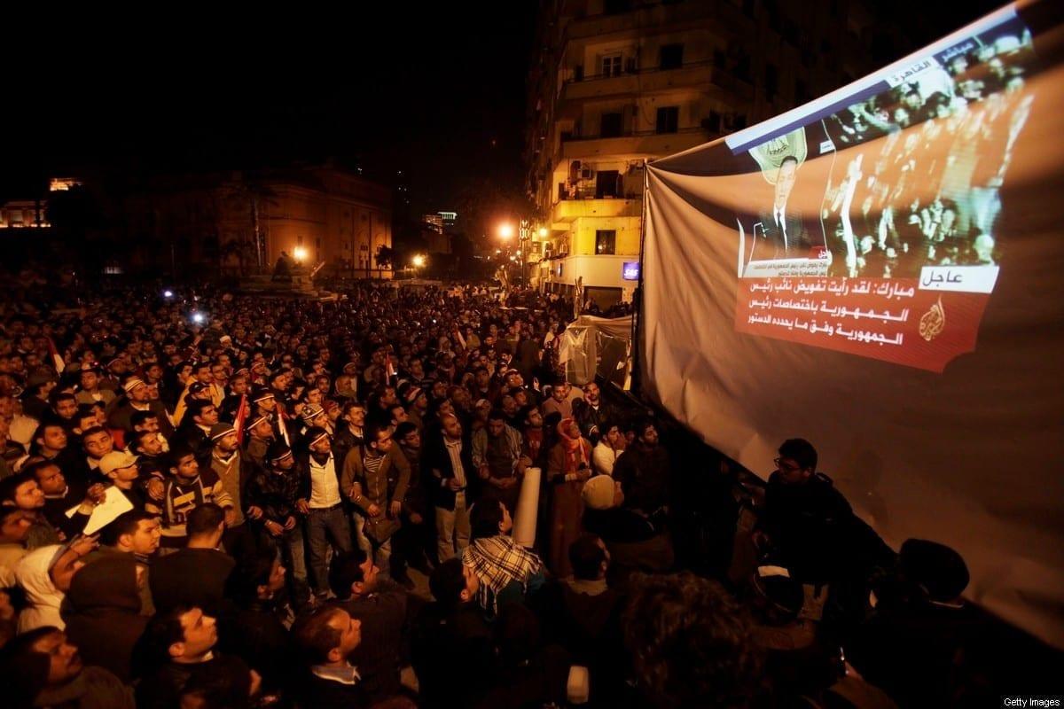 Manifestantes e soldados antigovernamentais assistem a um programa de TV na Praça Tahrir enquanto o presidente, Hosni Mubarak, faz um anúncio, em 10 de fevereiro de 2011, no Cairo, Egito. [Kuni Takahashi/Getty Images]
