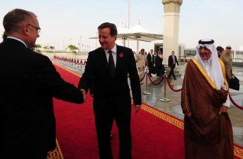 Um oficial não identificado cumprimenta o primeiro-ministro britânico David Cameron (C) enquanto caminha com o emir saudita de Meca, príncipe Khalid bin Faisal bin Abdulaziz (R), após sua chegada a Jeddah em 6 de novembro de 2012 [Amer Hilabi/ AFP via Getty Images]
